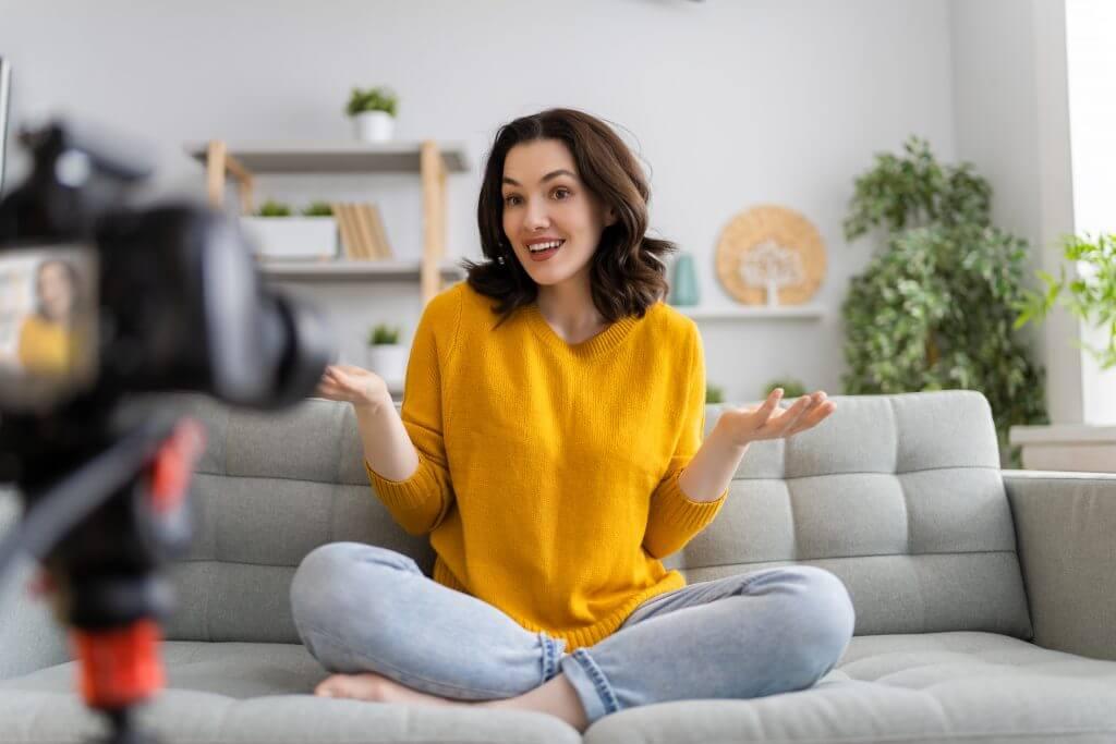 ragazza che parla davanti ad una telecamera sul divano di casa in relax